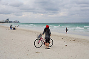A woman with a bicycle stands looking out to sea over the Atlantic Ocean fromSouth Beach Miami. Bikes are a very popular way of getting around the area