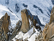 Rock climbers ascend Aiguille du Midi on Mont Blanc massif above a field of massive glaciers, Chamonix, France, Europe.