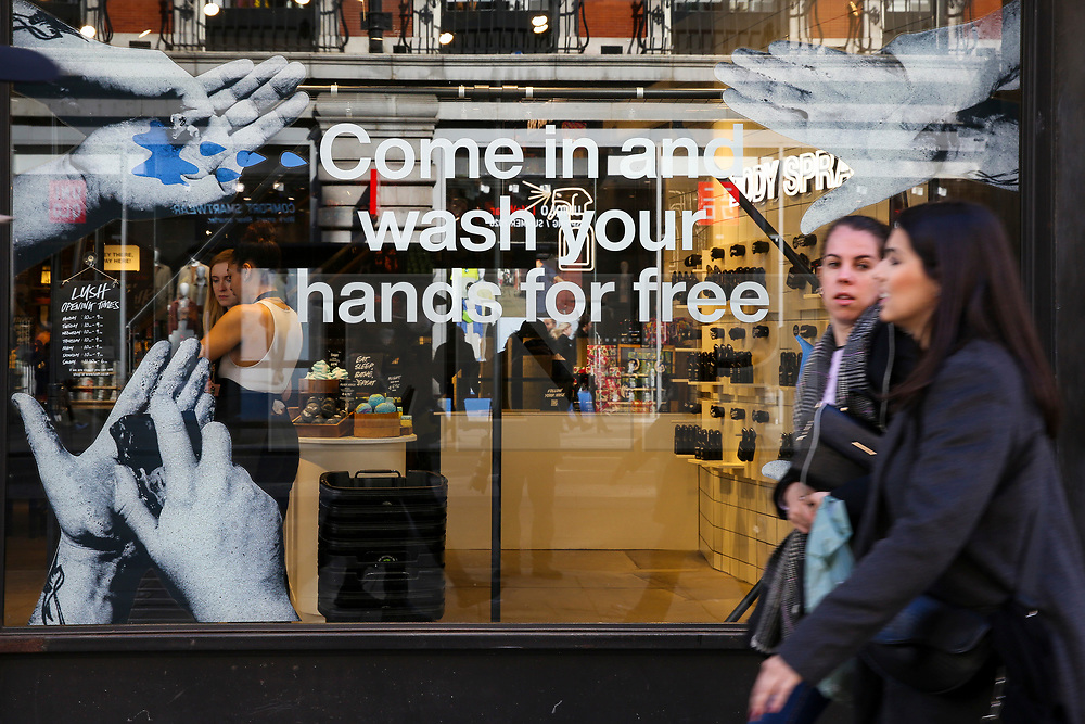 """© Licensed to London News Pictures. 11/03/2020. London, UK. Shoppers walk past a """"COME IN AND WASH YOUR HANDS FOR FREE' window display on Oxford Street. Chancellor RISHI SUNAK has unveiled a £30bn package to help the economy get through the coronavirus outbreak in the UK. Photo credit: Dinendra Haria/LNP"""