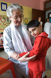 RAWALPINDI, PAKISTAN - NOV-01-2006 - An orphaned girl is cared for at the St. Joseph Hospice. The hospice was started by Father Francis O'Leary, an Irish missionary, in 1964. Franciscan nuns of the Missionaries of Mary, run the hospice and have a fully trained staff of 26 Pakistani nurses aides and volunteer doctors. The hospice, orphanage and free clinic has 60 beds for resident patients and treats 80-90 out patients daily.  All medical services are free of charge to resident patients at St. Joseph's, regardless of the cost, duration or type of treatment required. The hospice is supported solely by donations.  (PHOTO © JOCK FISTICK)