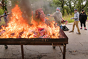 12 SEPTEMBER 2020 - DES MOINES, IOWA: TIM EARP throws US flags into the fire during a flag retirement ceremony at Glendale Cemetery in Des Moines. About 10 volunteers came to the cemetery Saturday morning to properly dispose of about 4,000 American flags. The flags had flown over veterans' graves, local businesses, and state offices. The US Flag Code calls for used American flags to be respectfully disposed of in a fire.    PHOTO BY JACK KURTZ