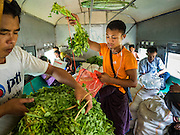 26 OCTOBER 2015 - YANGON, MYANMAR: Men sort vegetables they are taking to Yangon on the Yangon Circular Train. The Yangon Circular Railway is the local commuter rail network that serves the Yangon metropolitan area. Operated by Myanmar Railways, the 45.9-kilometre (28.5mi) 39-station loop system connects satellite towns and suburban areas to the city. The railway has about 200 coaches, runs 20 times daily and sells 100,000 to 150,000 tickets daily. The loop, which takes about three hours to complete, is a popular for tourists to see a cross section of life in Yangon. The trains run from 3:45 am to 10:15 pm daily. The cost of a ticket for a distance of 15 miles is ten kyats (~nine US cents), and for over 15 miles is twenty kyats (~18 US cents).     PHOTO BY JACK KURTZ