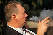 A gentleman dressed in a pin-stripe suit favoured by older workers in England, exhales the smoke from a fat cigar during a lunch-hour in Trinity Square in the City of London. The man is overweight and leads an unhealthy lifestyle, his chin overlapping his striped shirt. The cigar is held at the tips of two fingers and we can see in profile the billowing of a smoky cloud  from the man's lips. Government statistics suggest that in 2001, 27% of adults aged 16 and over smoked cigarettes in England; 28% of men and 25% of women. 66% of smokers in England wanted to give up smoking but more than 120,000 deaths were caused by smoking in the UK in 1995; that is, one in five of all deaths.