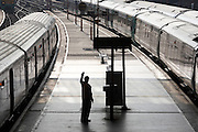 With a hand raised to the driver, a station employee waves the departure of a train at London Bridge mainline station.