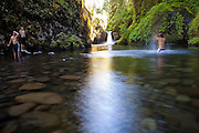Young men wade into Eagle Creek below Punchbowl Falls, Columbia River Gorge National Scenic Area, Oregon.