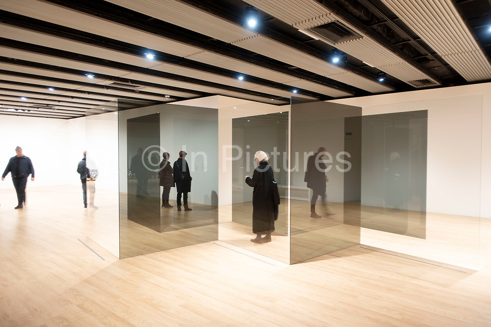 Visitors interacting with artworks at the Space Shifters exhibition at the Hayward Gallery on 16th December 2018 in London, United Kingdom. The exhibit was a major group show of sculptures and installations that explored perception and space, featuring 20 artists. Standing Walls, 1969/2016, by Larry Bell.