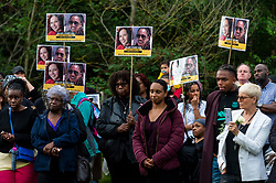 © Licensed to London News Pictures. 03/08/2021. LONDON, UK.  People holding photos of Bibaa Henry and Nicole Smallman at a vigil at Barn Hill Pond, Fryent Country Park near Wembley to remember the lives of sisters Bibaa Henry and Nicole Smallman, on what would have been Nicole's 29th birthday.  The sisters were murdered in the park in June 2020 whilst celebrating Bibbaa's birthday.  Reclaim These Streets have worked with former Archdeacon of Southend, the Ven. Wilhelmina (Mina) Smallman, the late sisters' mother, to organise the vigil and attendees were encouraged to wear green and purple, the sisters' favourite colours, or light a candle.  Photo credit: Stephen Chung/LNP