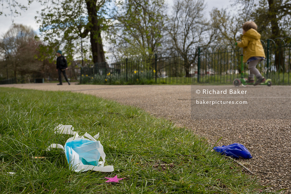 At the beginning of the second week of the UK's Coronavirus lockdown and in accordance with government guidelines for social distancing and local daily exercise, a used discaded surgical mask and glove lies in the grass alongside passing young child on a scooter in Ruskin Park, a green public space in the borough of Lambeth, south London, on 30th March 2020, in London.