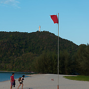 People leaving Tanjung Rhu beach with red flag, Langkawi, Malaysia