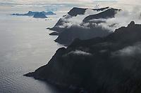 Mountain peaks emerge from the clouds in the west of Moskenesøy, Lofoten Islands, Norway