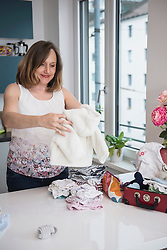Pregnant woman folding baby clothes and smiling in the kitchen, Munich, Bavaria, Germany