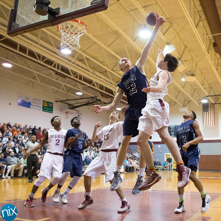 Jay M Robinson's Jordan McKenzie hits a basket while being covered by Hickory Ridge's Daniel Heidtke during a 3A west state basketball playoff game Thursday, February 25, 2016 at Jay M Robinson High School in Concord, NC. Photo by JASON E. MICZEK - www.miczekphoto.com