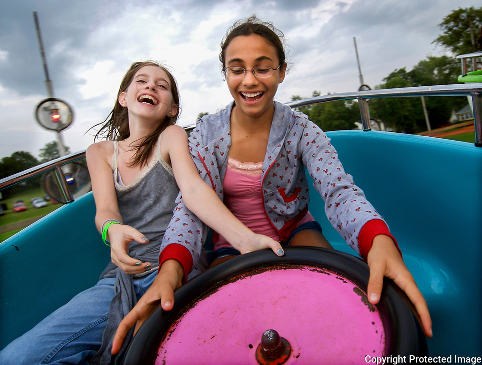 """Ashley Miltich, 12, left, helps friend Analise Berkemeier, 11, to spin the wheel on the Tip Top ride at the Family Fall Festival held at St. John School and Jackson Catholic Middle School during a day in the life of Jackson County on Sept. 7, 2007. The faster the girls spin the wheel the faster the car turns. """"It's bouncy and exciting,"""" said Analise. """"It also makes you dizzy."""""""