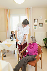 Caregiver checking blood pressure of senior woman in rest home, Bavaria, Germany