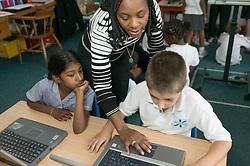 Teacher showing school children how to use computers in classroom,