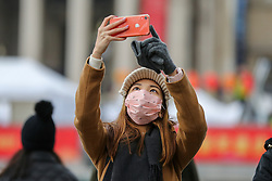© Licensed to London News Pictures. 25/01/2020. London, UK. A woman in Trafalgar Square wearing face mask as a precaution against the outbreak of the Coronavirus takes a photograph of the Chinese lanterns decorated for the celebrations of the Chinese New Year, the Year of the Rat. Photo credit: Dinendra Haria/LNP