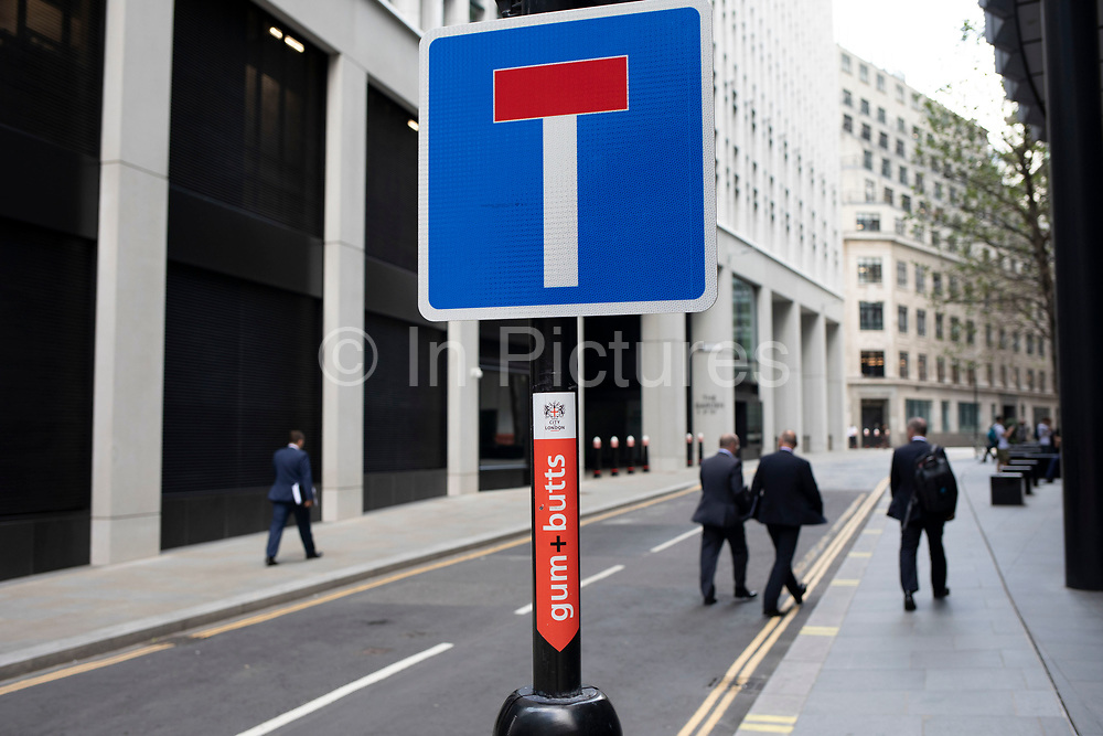 City workers walk past a dead end sign in the City of London, England, United Kingdom. Possibly a sign for tough economic times to come.