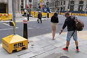 A man drops a used beer can in the street before walking on, near Bank underground station, outside the Bank of England, in the Square Mile, the capital's financial district, on 6th August 2020, in London, England.