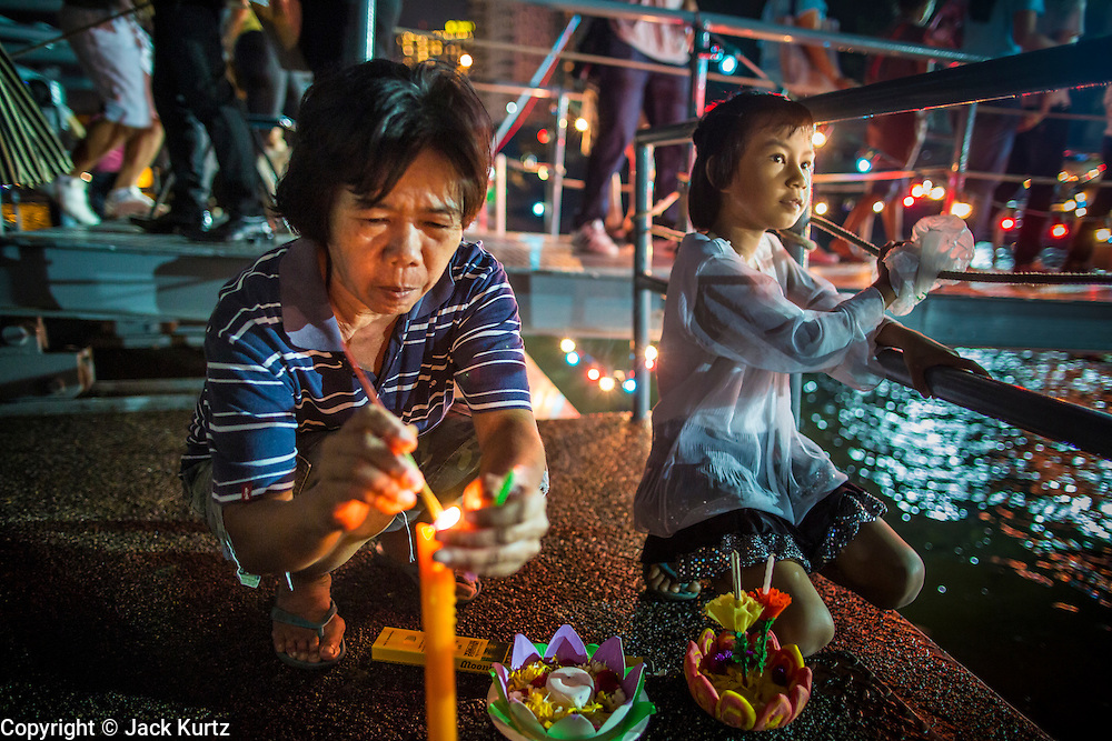 28 NOVEMBER 2012 - BANGKOK, THAILAND: A woman lights the candles on her krathong before placing it in the Chao Phraya River on Loy Krathong at Wat Yannawa in Bangkok. Loy Krathong takes place on the evening of the full moon of the 12th month in the traditional Thai lunar calendar. In the western calendar this usually falls in November. Loy means 'to float', while krathong refers to the usually lotus-shaped container which floats on the water. Traditional krathongs are made of the layers of the trunk of a banana tree or a spider lily plant. Now, many people use krathongs of baked bread which disintegrate in the water and feed the fish. A krathong is decorated with elaborately folded banana leaves, incense sticks, and a candle. A small coin is sometimes included as an offering to the river spirits. On the night of the full moon, Thais launch their krathong on a river, canal or a pond, making a wish as they do so.    PHOTO BY JACK KURTZ