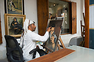 Mohammed Rageh, an artist at Souk Waqif in Doha, Qatar, works outdoors on a painting of a man with an iPhone. Souk Waqif is a popular pedestrian zone in Doha, and this photograph was taken from a public walking path