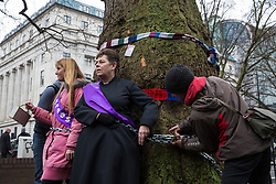 London, UK. 12th January, 2018. Anne Stevens (c), the vicar of St Pancras church, is chained to a tree outside Euston station during a protest against the HS2 high-speed rail link. The protest formed part of a campaign by local residents against the planned felling of mature London Plane, Red Oak, Common Whitebeam, Common Lime and Wild Service trees in Euston Square Gardens to make way for temporary HS2 sites for construction vehicles and a displaced taxi rank.