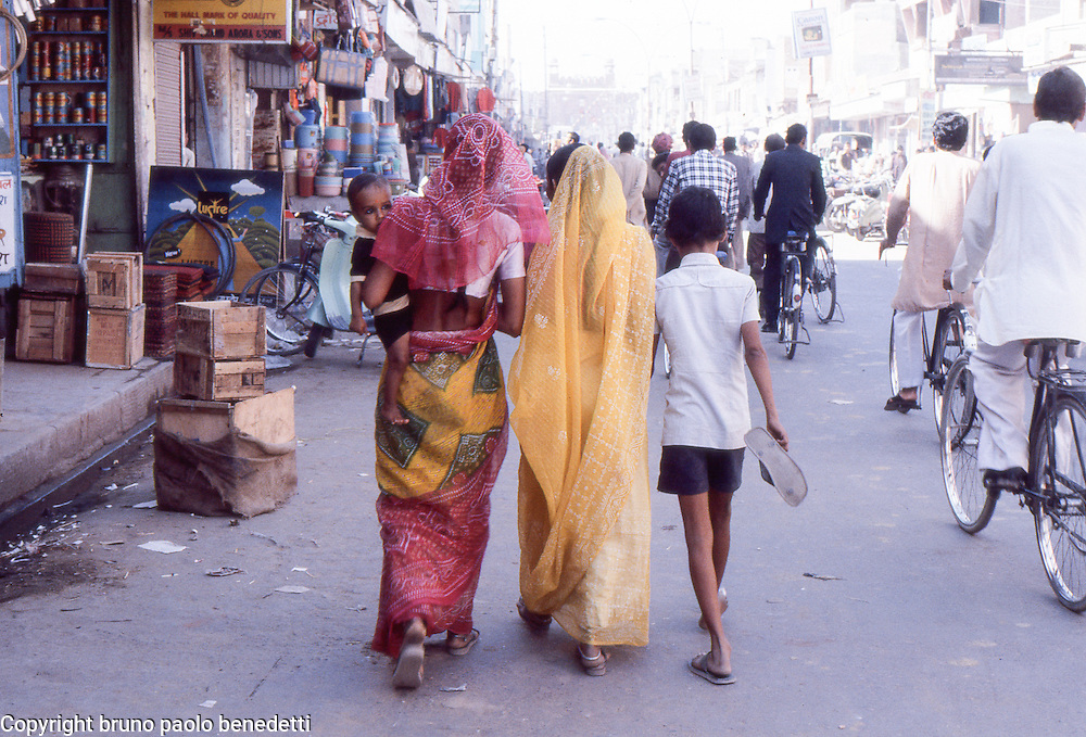 view from behind of walking indian women in sari with kids along shops in indian town street