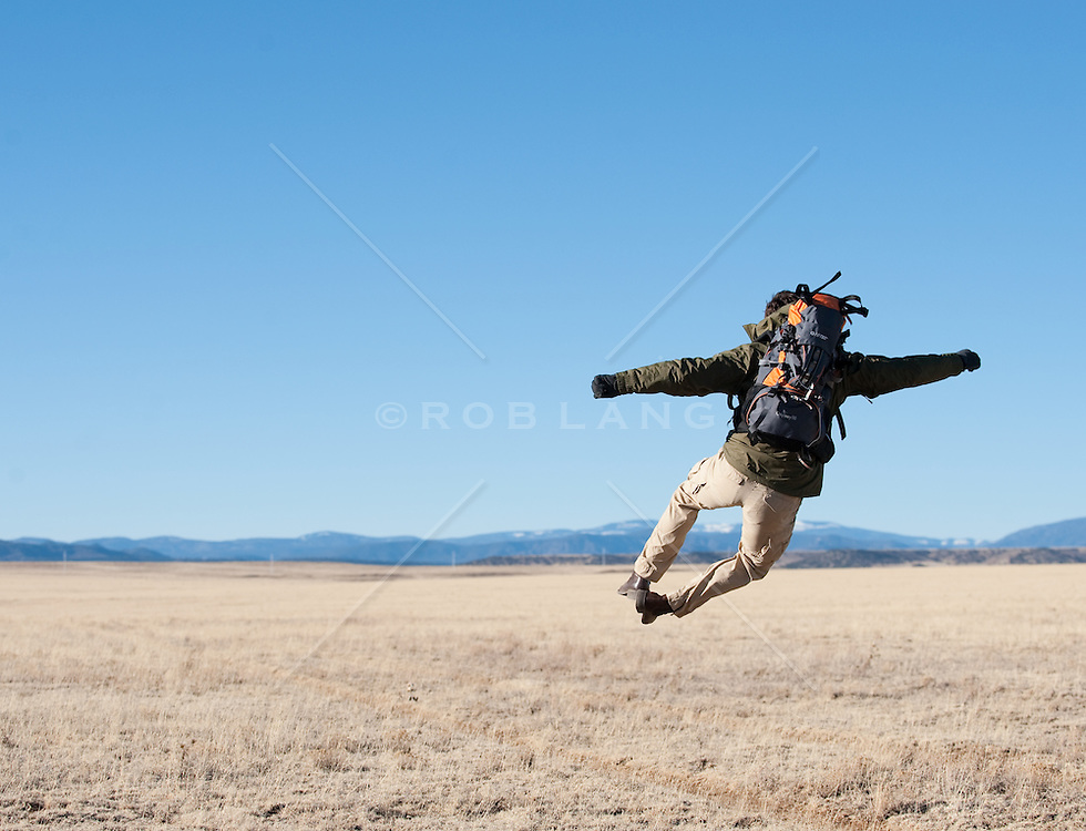 Backpacking man leaping and clicking his heels while hiking in the high desert of New Mexico