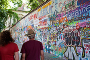 Two people a man and a woman look at the Lennon wall with grafitti all over it in memory of John Lennon, Prague, Czech Republic. .
