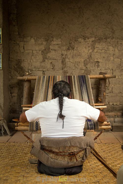 Man using a backstrap loom, a type dating from Inca times, Otavalo, Ecuador, South America