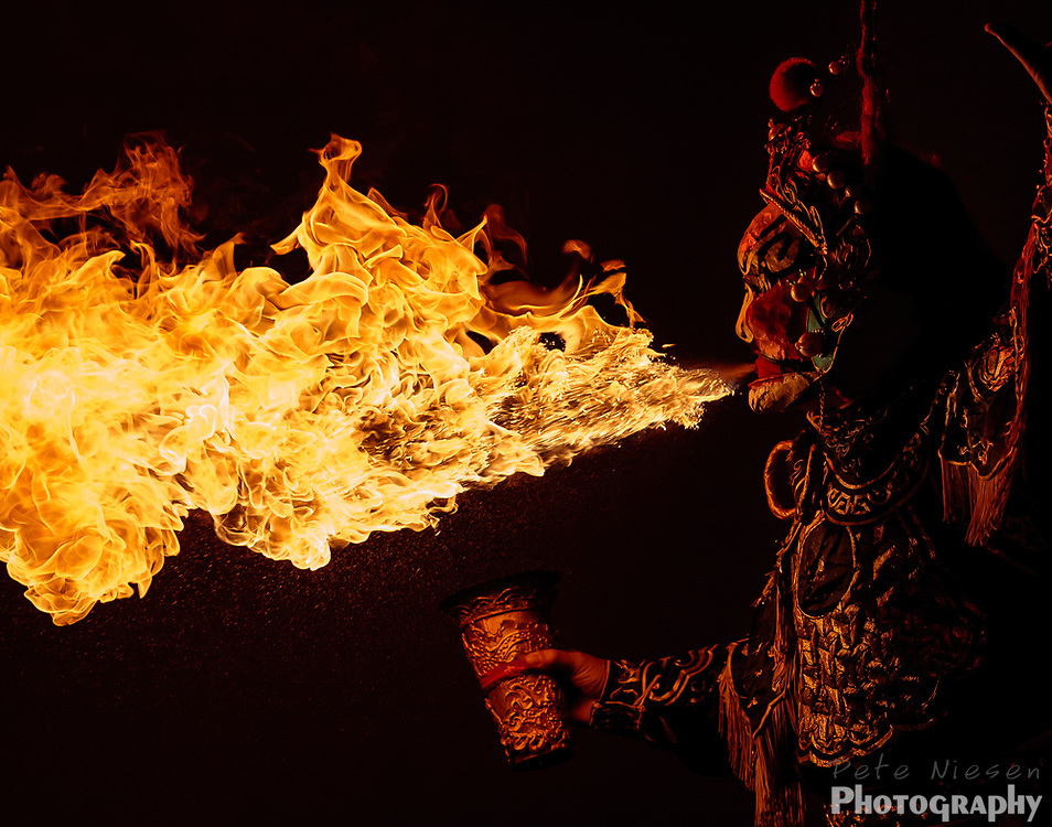 CHENGDU, CHINA: Fire breather shoots a spray of fire during a performance of Sichuan opera. Chengdu, China