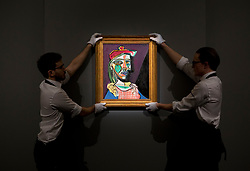 """© Licensed to London News Pictures. 22/02/2018. LONDON, UK. Two members of staff hold """"Femme au béret et à la robe quadrillée"""" (Marie-Thérèse Walter) (1937) by Pablo Picasso on display at Sotheby's photo call for highlights from their forthcoming sales of Impressionist, Modern, Surrealist and Contemporary Art. Photo credit: ISABEL INFANTES/LNP"""