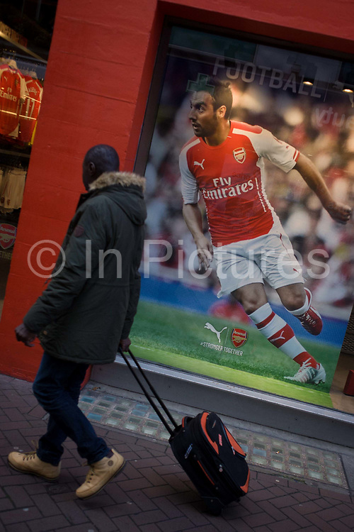 Diagonal angle of Arsenal footballer and man pulling luggage, in Carnaby Street, London. In a coincidence of diagonal slants, we see the Arsenal footballer Mathieu Flamini on the field during a football game. His image appears in the shop window of sports brand Puma. Sharing the slant is a man who tows his luggage behind him, the diagonals matching the scene.