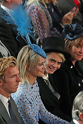 Poppy Delevingne (left) and Cara Delevingne attend the wedding of Princess Eugenie to Jack Brooksbank at St George's Chapel in Windsor Castle.