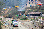 A truck driving along  the Nakkhu river bed past the cremation of a local man taking place at Tikabhairab Temple on the 13th of March 2020 in Tikabhairab, Lalitpur, Kathmandu District, Bagmati Pradesh, Nepal. (photo by Andrew Aitchison / In pictures via Getty Images)