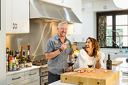 Tim and Emilie Love enjoying wine and a snack in the kitchen of their home in Fort Worth, Texas USA. The wine is Tim's own label.