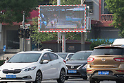 "Pedestrians who jay walk or who cross when there is a red light can be fined 20 yuan after they do this three times. They are named and shamed after the offence. An image of their face and name appears of the video screen for all to see. This is part of a new control with face recognition camera software installatioin at traffic lights. Offences and misdemeanours such as these can contribute to a citizen's social credit rating. They lose points for a traffic ticket but gain points for an ""exemplary city level heroic act"". A poor social credit score can lead to bans from travel, certain schools, luxury hotels, government positions and even dating apps. Traffic lights at crossroads. Beijing outskirts. China"