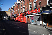 Brick Lane almost deserted and the famous curry houses or Indian and Bangladeshi restaurants closed due to Covid-19 on what would normally be a busy, bustling market day with hoards of people out to shop, eat and socialise on 22nd March 2020 in London, England, United Kingdom. All of the East End Sunday markets have been affected by the Coronavirus outbreak, with some completely closed and some currently partially open. Coronavirus or Covid-19 is a new respiratory illness that has not previously been seen in humans. While much or Europe has been placed into lockdown, the UK government has announced more stringent rules as part of their long term strategy, and in particular social distancing.