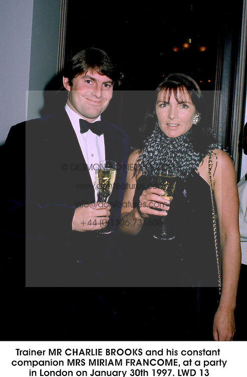 Trainer MR CHARLIE BROOKS and his constant companion MRS MIRIAM FRANCOME, at a party in London on January 30th 1997.LWD 13