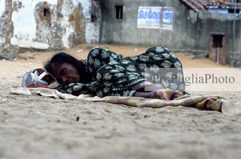 TAMIL NADU, MARCH 1994.An old woman is lying on the floor. She is wresting her head on her few belongings.