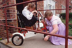 Mother helping young girl with disability to ride adapted tricycle,