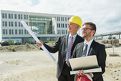 Two businessmen with hard hats on construction site