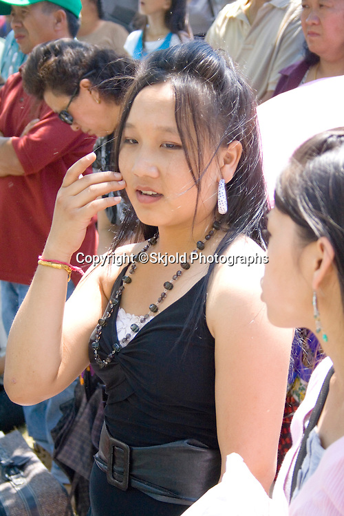 Attractive Hmong Asian teen talking on cell phone in festival crowd. Hmong Sports Festival McMurray Field St Paul Minnesota USA