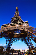 Eiffel Tower and park with blue sky and people below.