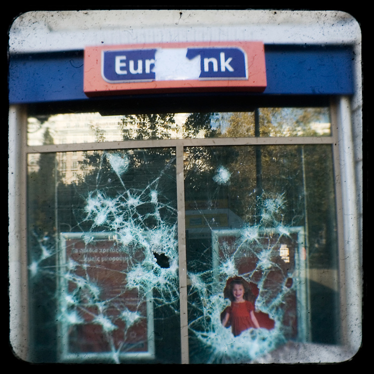 The shattered windows of Eurobank in Syntagma square.<br /> <br /> Following the murder of a 15 year old boy, Alexandros Grigoropoulos, by a policeman on 6 December 2008 widespread riots, protests and unrest followed lasting for several weeks and spreading beyond the capital and even overseas<br /> <br /> When I walked in the streets of my town the day after the riots I instantly forgot the image I had about Athens, that of a bustling, peaceful, energetic metropolis and in my mind came the old photographs from WWII, the civil war and the students uprising against the dictatorship. <br /> <br /> Thus I decided not to turn my digital camera straight to the destroyed buildings but to photograph through an old camera that worked as a filter, a barrier between me and the city.