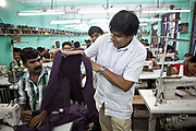 A Nepalese factory owner inspects the work of one of his male employees in Surijha Traders garment factory in Kathmandu, Nepal. He is inspecting a silk purple waistcoat. The garments made in this factory are exported all over the world.  The factory works closely with the Friends of Needy Children organization in providing fair employment opportunities for young Nepalese men and women.