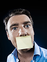 caucasian man mouth shut by a note paper portrait isolated studio on black background