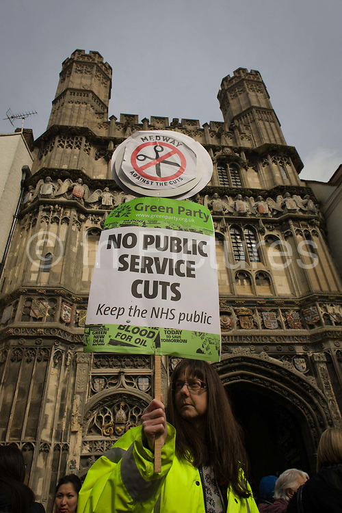 A Green Party protester demonstrates against the Tory coalition below Church Gate in Butter Market, holding up a placard against public service cuts during the enthronement for the new Archbishop of Canterbury, Justin Welby. Her protest is about coalition plans over the NHS, holding a placard in Butter Market in the centre of Canterbury, urging the government to keep the country's National Health Service out of private hands, to keep it as a government organisation, run by Jeremy Hunt and overseen by his boss, Cameron. The town of Canterbury hosted the enthronement of the Church of England's new Archbishop, allowing Medway locals to voice their concerns.