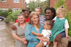 Multiracial family group standing outdoors; with three generations,