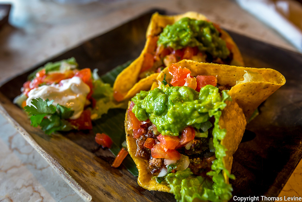 Hard Shell tacos with lettuce, cilantro, tomato, ground beef, and sour cream as served in Indonesia.