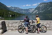 Cyclists admire the view from the bridge at Ribcev Laz and out into Lake Bohinj, on 19th June, in Lake Bohinj, Sovenia.